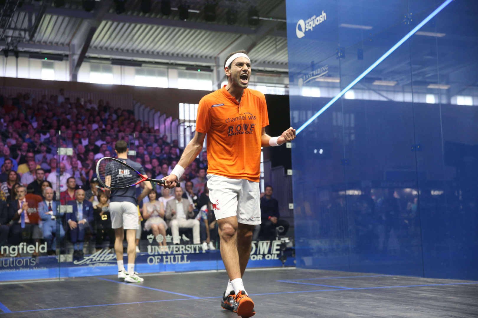 2 men playing squash in a court in front of a crowd